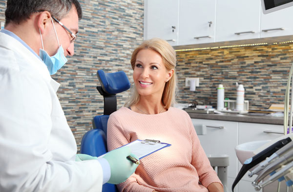 Woman talking to our dentist before a dental exam at Wanserski Dental Center for Complex Dentistry in Wausau, WI