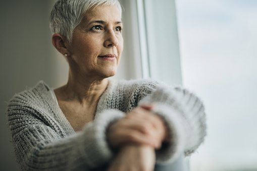 Woman with short hair looking out of a window happy with her dental implants from Wanserski Dental Center for Complex Dentistry